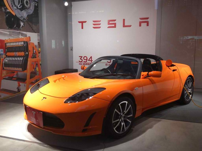 An orange Tesla Roadster is on display in front of a Tesla sign.